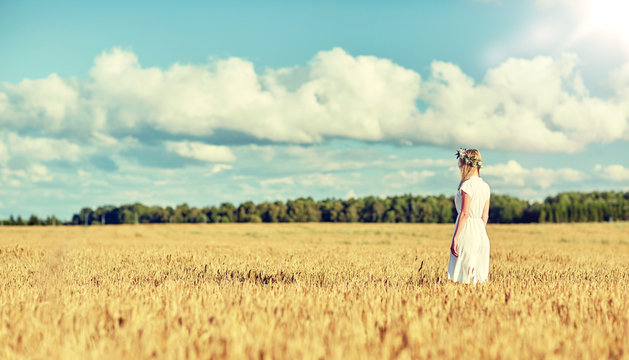 happiness, nature, summer holidays, vacation and people concept - smiling young woman in wreath of flowers and white dress on cereal field