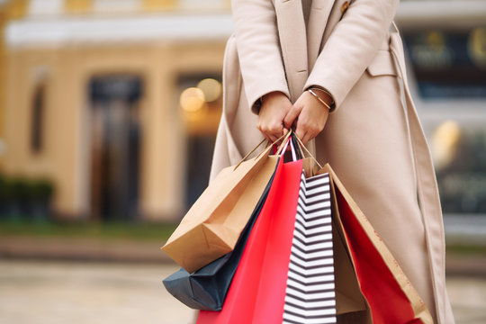 Shopping bags in the hands. Hand of young woman with multi-coloured bags with purchases. Beautiful girl holding shopping bags on the city street. Consumerism, shopping, sales, lifestyle concept.