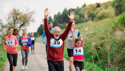 Large group of multi generation people running a race competition in nature. Fototapete