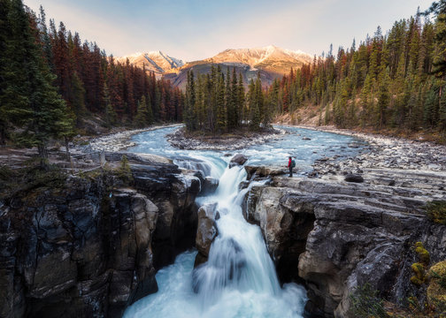 Sunwapta Falls is pair of of the Sunwapta river with traveler standing in autumn forest at sunset