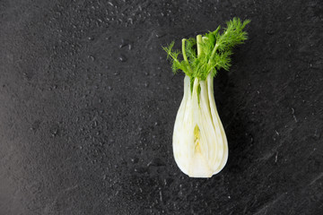 vegetable, food and culinary concept - fennel on slate stone background
