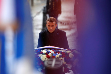 French President Emmanuel Macron lays a wreath of flowers at the tomb of the Unknown Soldier under the Arc de Triomphe as part of commemorations marking the 101st anniversary of the