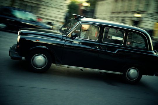 Black cab driving in motion blur on a London street