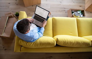 Top view of mature man sitting on sofa in unfurnished house, using laptop.