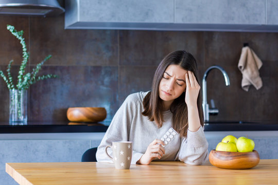 Brunette girl is sitting at table in kitchen and holding hand on head temple. Young woman is feeling bad and going to take painkiller pills. Sudden attack of migraine and headache. Effects of stress.
