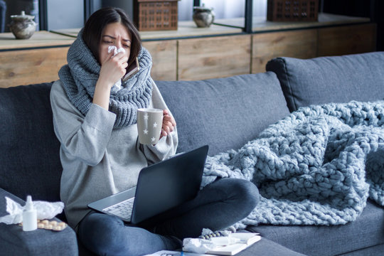 Ill brunette girl is sitting at sofa and working remotely on laptop. Female is blowing out snot, having fever and headache. Young woman is treated at home, took sick leave. Winter cold and flu concept