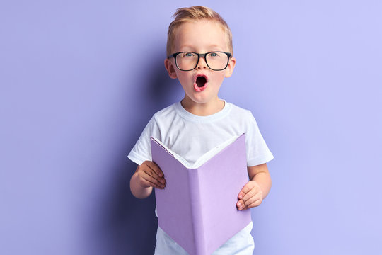 Lovely boy wearing white t-shirt and glasses on eyes reading book with purple cover, stand in shock after reading, bright emotions of kid boy. Isoated over purple background