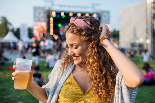 A young woman with drink dancing at summer festival.