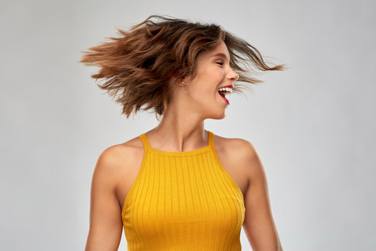 emotions and people concept - happy laughing young woman in mustard yellow top shaking head over grey background