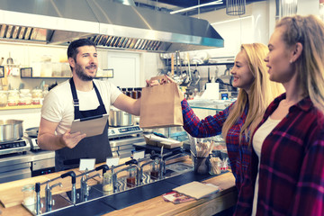 Waiter serving takeaway food to customers at counter in small family eatery restaurant
