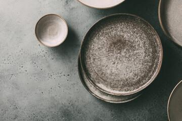 Obraz Empty ceramic bowls and plates on a dark background. Top view, copy space. - fototapety do salonu