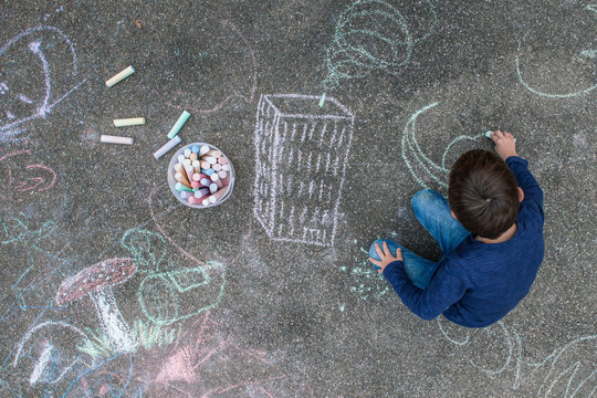 Young boy drawing on the sidewalk with chalk
