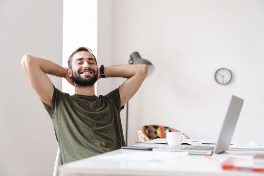 Image of relaxed man sitting at desk and holding hands behind his head
