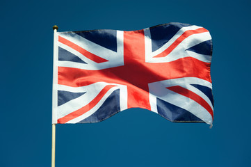 Single British Union Jack flag flying on a flag pole in sunny bright blue sky Wall mural
