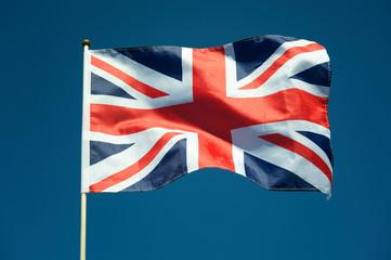 Single British Union Jack flag flying on a flag pole in sunny bright blue sky Fotoväggar