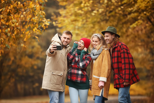 Friends taking selfie in autumn park