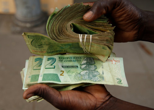 A street vendor poses as he displays bond notes, before the introduction of new currency in Harare