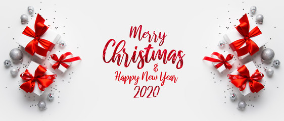 Wall Mural - Christmas and New Year holiday background. Xmas greeting card. Christmas red ribbon gifts and ornaments on white background top view. Flat lay