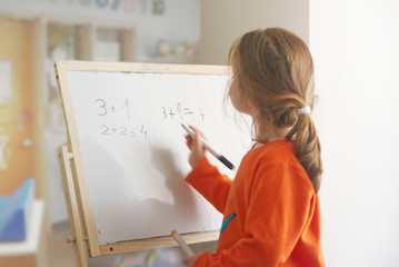 Caucasian child girl resolving mathematical addition operation on a white board in a classroom. Empty copy space for Editor's text.