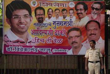 A policeman stands in front of a hoarding with the picture of Aaditya Thackeray a leader of Shiv Sena, a regional political party, in Mumbai