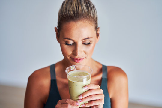 Adult woman drinking healthy smoothie after workout