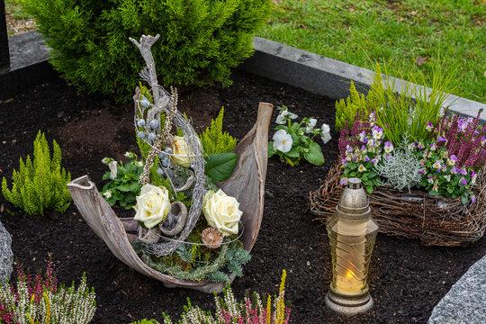 Geschmücktes Grab mit leuchtendem Grablicht