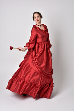 full length portrait of a brunette girl wearing a red silk victorian gown. holding a single rose on a white studio background.