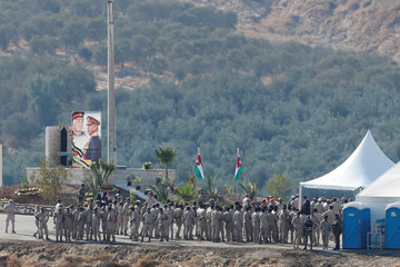 Jordanian soldiers gather near a tent and a picture depicting Jordanian King Abdullah and his father, late King Hussein, in the border area between Israel and Jordan, as seen from the Israeli side