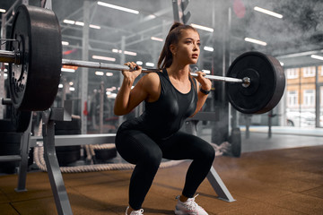 Charming strong female powerlifter dressed in black sportswear and white sneakers, doing squats,...