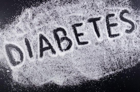 The word DIABETES on the spilled sugar on black background. Harm of sugar, diabetes disease medical concept.