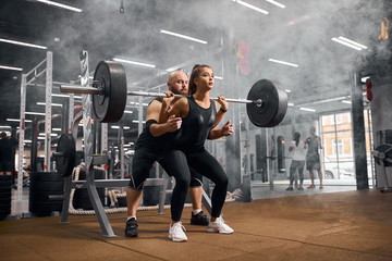 Young active pair of sporty people training in modern sports hall, fit woman squatting with heavy barbell, brutal man insuring standing behind, side shot