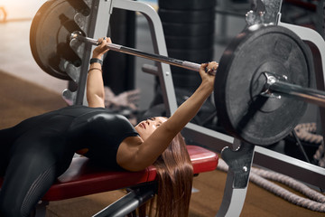 Sporty young female powerlifter with long straight hair, lying under iron barbell, getting ready for weight lifting as part of fitness program, side shot