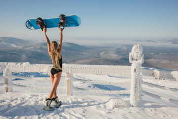 Papiers peints Glisse hiver Woman wearing bikini and t-shirt with snowboard standing on snow mountain top in ski resort. Beautiful mountains view background, frozen sunny morning, frost on the binocular