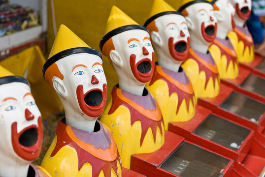 Brightly colored sideshow clowns at a circus..