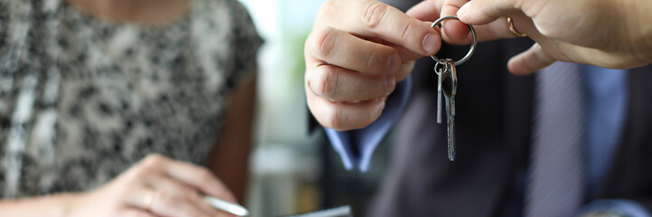 Businessman giving house keys to new owner after signing profitable contract. Woman holding papers with important agreemant. Real estate market and business concept. Blurred background