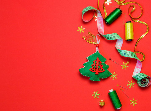 sewing christmas decoration with toy christmas tree on red background