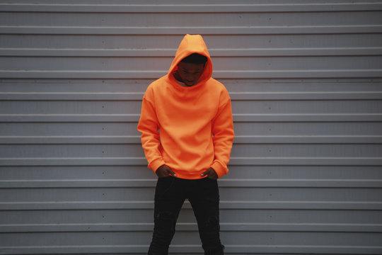 African American man wearing blank orange hoodie standing against grey wall