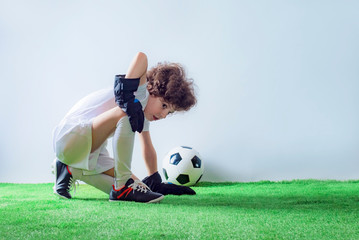 Cute cheerful curly-haired boy soccer goalkeeper on his knees, hands clasped in prayer and looking into the empty space. Gray background.