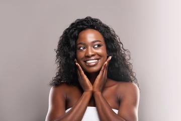 Fototapete - Beautiful black woman happy about her flawless skin on cheeks