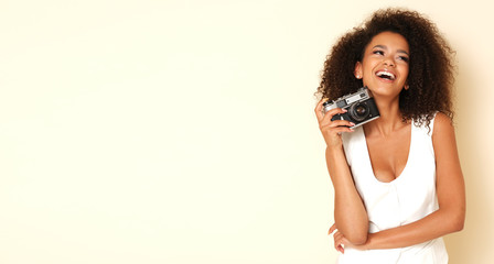 Happy, afro-american model with old-fashioned camera.