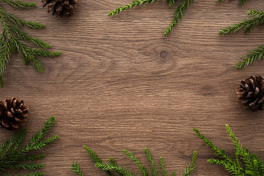 Wooden table with Christmas decoration including pine branches and pine cones. Merry Christmas and happy new year concept. Top view with copy space, flat lay.