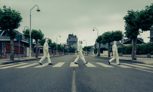 People with bacteriological protection suits crossing a crosswalk in a row