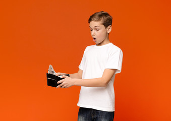 Shocked boy looking at lots of money in found wallet