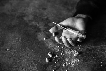 Fototapeta Addict man dead after inject drug overdose with syringe injection heroin to hand. narcotic addiction concept, International Day Against Drug Abuse. black and white picture obraz