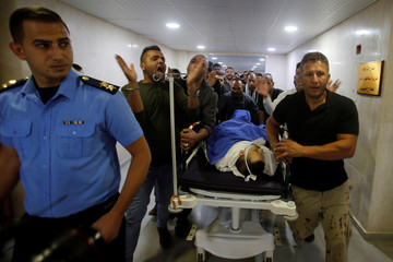 People wheel the dead body of Palestinian man Omar al-Badawi at a hospital in Hebron, in the Israeli-occupied West Bank