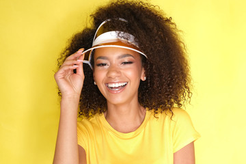 Such a beautiful smile! Afro girl in yellow clothes on yellow background.