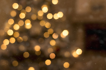 Abstract Christmas background with blurred Christmas tree and lights on back. Boken effect. Disfocus image.