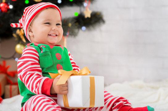 Happy baby enjoying first Xmas gift at home