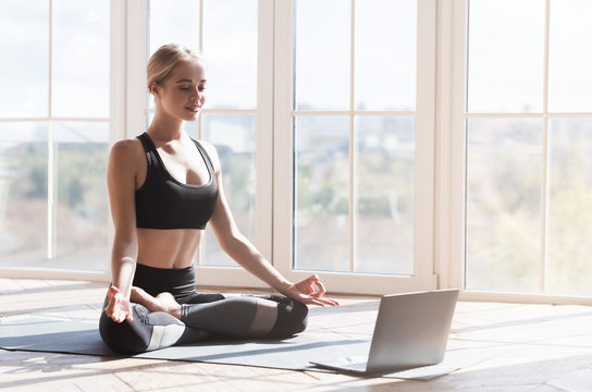 Cheerful girl doing yoga at home, looking at laptop screen