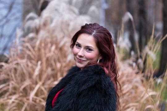 Medium horizontal photo of pretty red haired young woman smiling seductively and wearing red dress under faux fur black coat standing in front of decorative grasses background